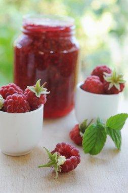 Jar of raspberry jam and fresh berries outdoor