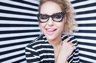 Attractive young blonde woman wearing glasses on stripy background