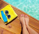 Fotografia donna su un molo in legno presso la piscina con accessori estate