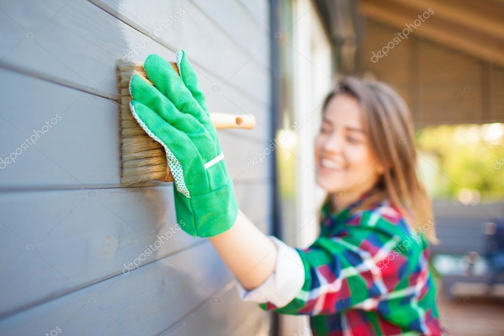 Young woman applying protective varnish