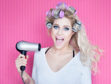 Woman with hair dryer and rollers