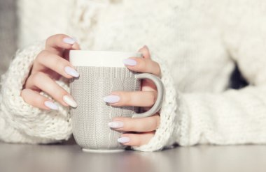 Woman's hands holding cup of hot coffee drink