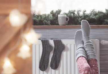 Woman warming up with feet on heater