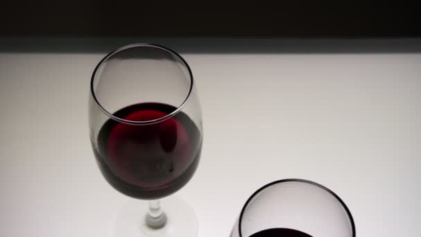 Red wine in two glasses on a light table. Top view. Slow motion, medium shot.