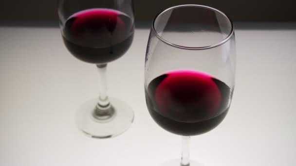 Červené víno ve dvou sklenicích na lehkém stolku. Horní pohled. Zpomalený pohyb, střední střela.