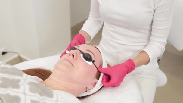 Kosmetikerin setzt Klientin Schutzbrille auf.