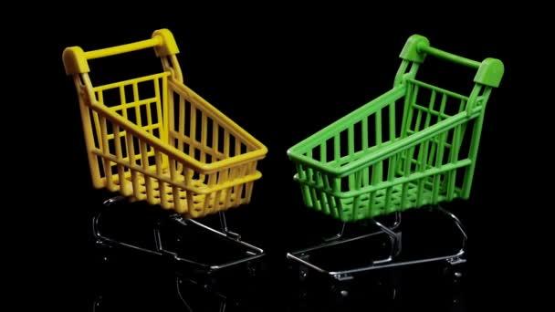 Dva prázdné nákupní košíky na černém pozadí, nákupní koncept. rotující