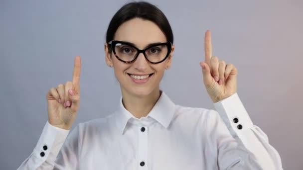 Nahaufnahme Porträt hübsche junge Frau zeigt mit zwei Fingern in die Kamera, isoliert auf weißem Hintergrund