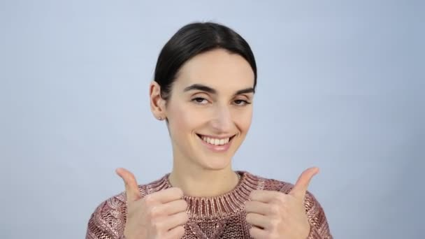 Close up shot of young positive woman with long hair looking at camera through ok-gesture, Beautiful brunette female with dark eyes has playful good mood.