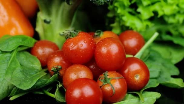 Cseresznyés paradicsom és más zöldséges saláta, spenótpaprika fekete alapon. Forgás