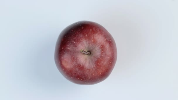 Red fresh apple rotates on a white background.