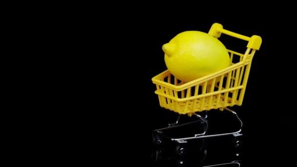 Citron ve žlutém nákupním košíku na černém pozadí. Rotace.