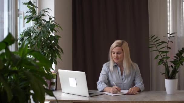 Női irodai alkalmazott keres információt laptop és dokumentumok, munkaközvetítő bróker