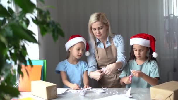 žena a dvě dcery vyřezávají sněhové vločky k Vánocům. Technologie a vzdělávání Kavkazský Blondýny Rodinný koncept
