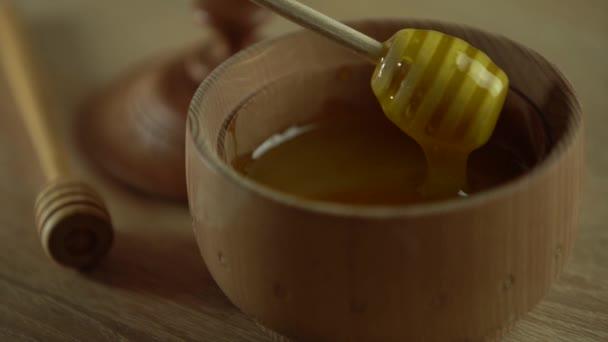 Z lžíce kape hustý med, zblízka. Med tekoucí med z lžíce