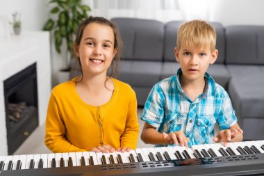 Brother and sister play the synthesizer. Children play at piano. family games