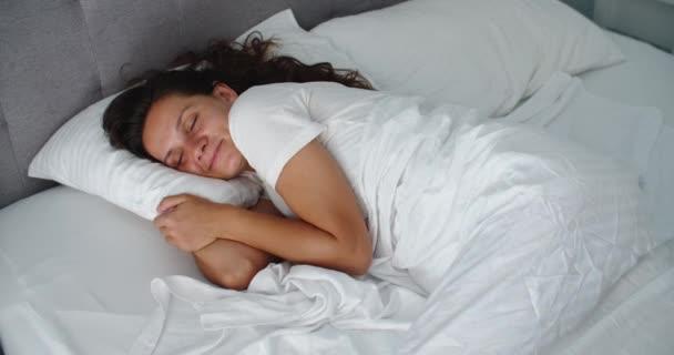 Dobré ráno. Atraktivní usmívající se mladá žena probouzející se plně odpočatá na bílém lůžku. Portrét krásné zdravé modelky dívka