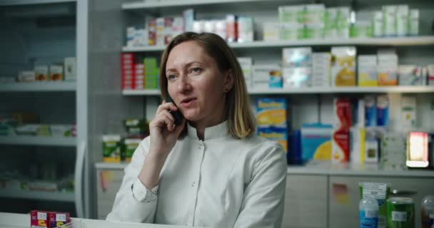 A pharmacist woman at a pharmacy advises a client by phone. Telephone call.