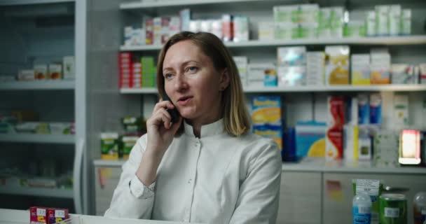 Eine Apothekerin in einer Apotheke berät eine Kundin telefonisch. Telefonat.