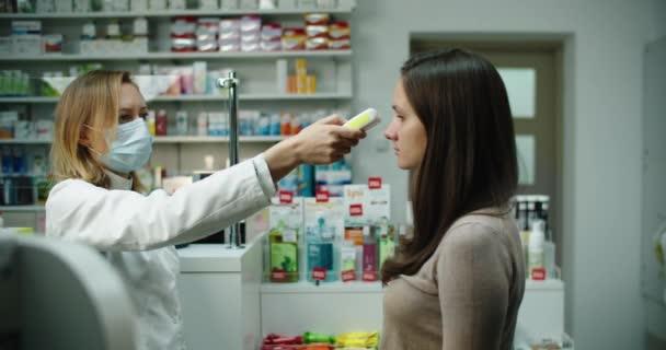 Apothekerin misst die Temperatur der Kunden am Eingang der Apotheke. Infektionsgefahr. Alle in medizinischen Masken.