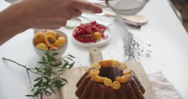 Ženy ručně sypou cukr na čerstvý dortík. Práškový cukr padá na čerstvý dokonalý sladký koláč. Kopírovat prostor pro text. Nápady a recepty na snídani nebo dezert