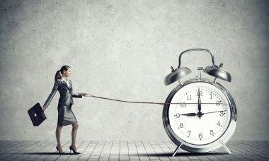 businesswoman holding alarm clock on lead