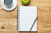 Poznámkový blok s kávou, zelené jablko a pera