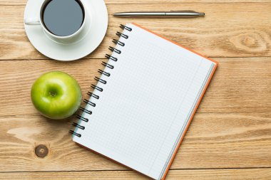 notepad with  coffee , green apple and pen