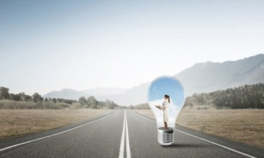 Young businesswoman trapped inside of light bulb on asphalt road stock vector