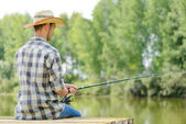 Fotografie Mladý muž sedí na molu s tyčinkou