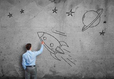 Businessman drawing rocket