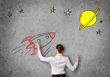 businesswoman drawing rocket on wall