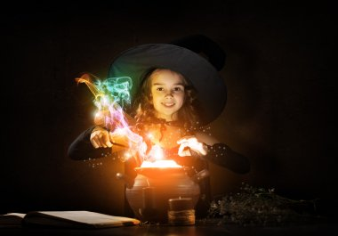 Little Halloween witch reading conjure from magic book above pot stock vector