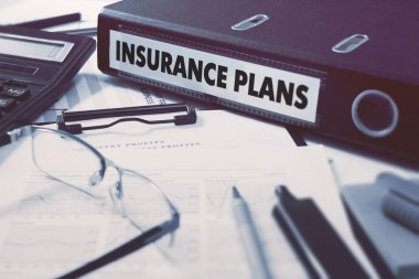 Insurance Plans on Ring Binder. Blured, Toned Image.