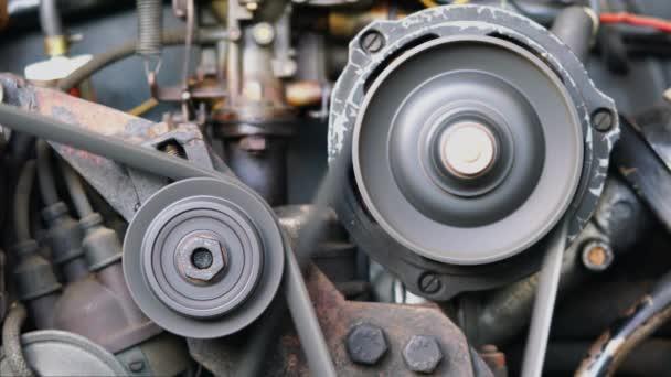 Motor starého auta běží. Uzavřený pohled na pohyb starého automobilového kovového kola motoru.