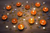 Fotografie Orange candles and yellow shining stars