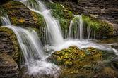 Vodopád teče z mechové skály