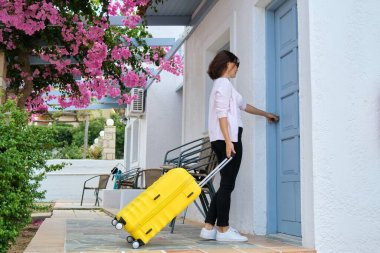 Outdoor, woman traveler with yellow suitcase opening closing door of the house