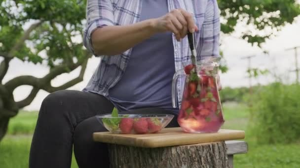 Zblízka ženské ruce dělat přírodní nápoj s jahodami a mátou