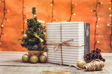 Present box with Christmas decorations and bokeh lights on a wooden table
