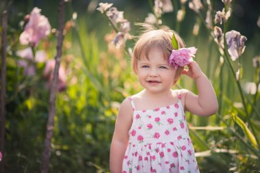 baby girl in summer garden with bright flowers