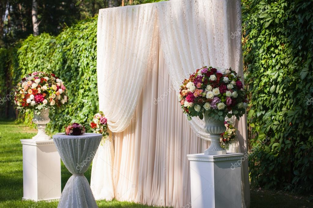 wedding arch with big flower bouquets on the green leaves backgr ...