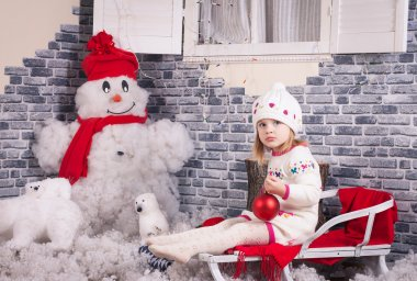 A little girl on the sleigh with red fir-tree ball in her hands. Backside decorated by  imitation of snow and snowman near the brick wall