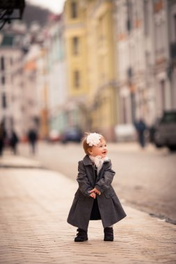 A little lady stand straight on the street