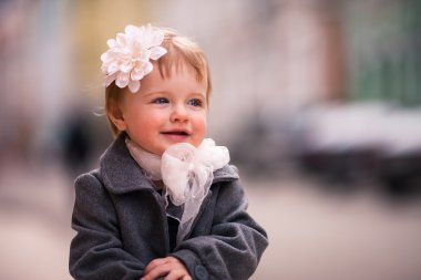 A portrait of cute little baby girl in gray coat on the street in old city with funny smile