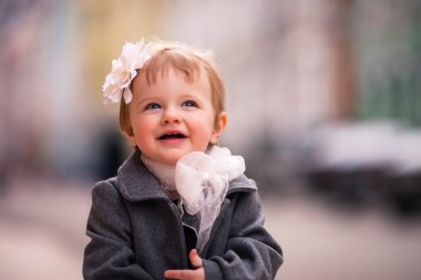 A portrait of little baby girl in gray coat on the street in old city with funny smile