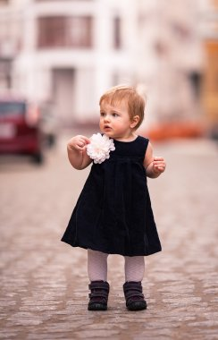 A little baby girl in dark dress with big white flower stands on the street