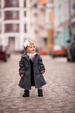 A little lady in grey coat and big flower in her hear stands on the street