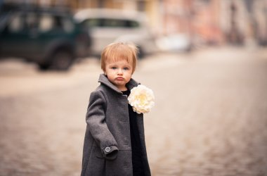 A portrait of little baby girl in gray coat stands on the street in old city with funny face
