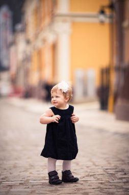 A little baby girl stands on the street